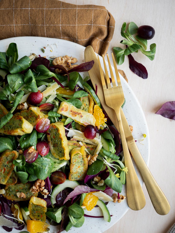 Wintersalat mit vegetarischen Maultaschen, warmen Weintrauben, gerösteten Walnüssen und Parmesanhobel